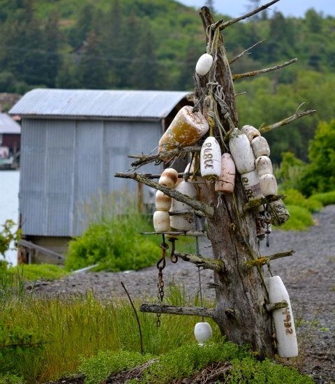 Old buoys collected on a spruce stump in Halibut Cove, Alaska.