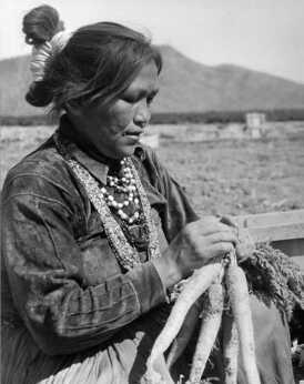 A Navajo woman ties carrots that were just harvested from the field in Maricopa County, Arizona. The Navajo are an example of both a matrilineal and matrilocal society. Property and clan membership are both inherited from the female lineage.