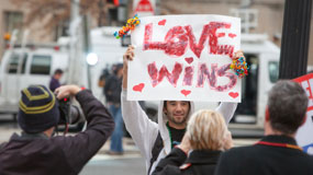 man holding sign that says 'love wins'