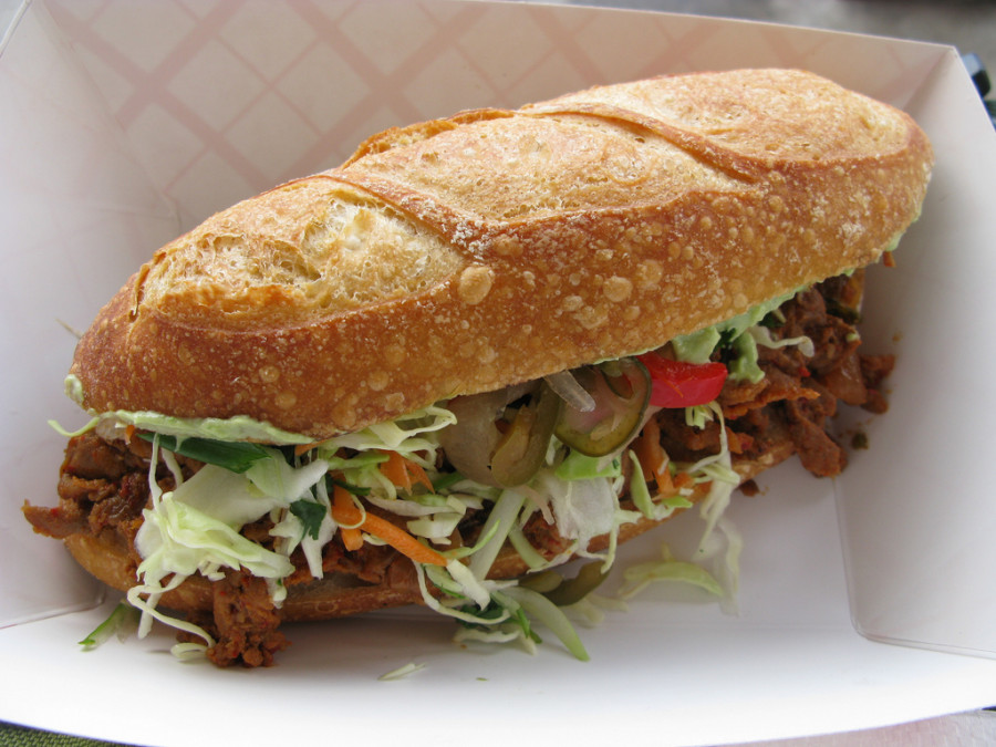 """From the menu board """"spicy pork, slaw, housemade pickled peppers & onions, guacamole and [some sauce I don't recall the name] served on a Columbia City Bakery roll"""" $7 and delicious."""