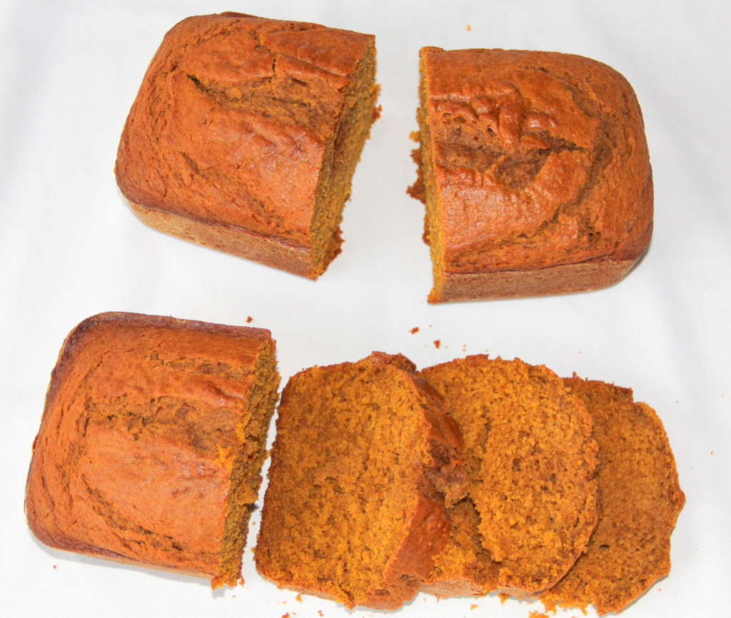 Two loaves of baked easy pumpkin bread, one sliced and ready to eat.