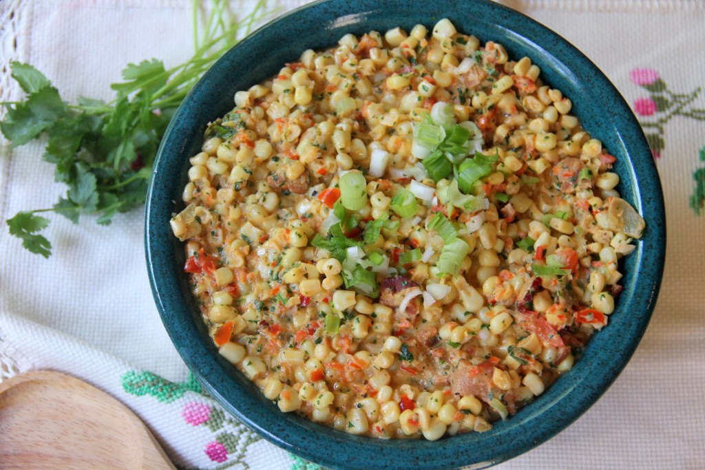 Mexican creamed corn with jalapenos, bacon, scallions, and cilantro is a great side dish for a potluck or cookout.