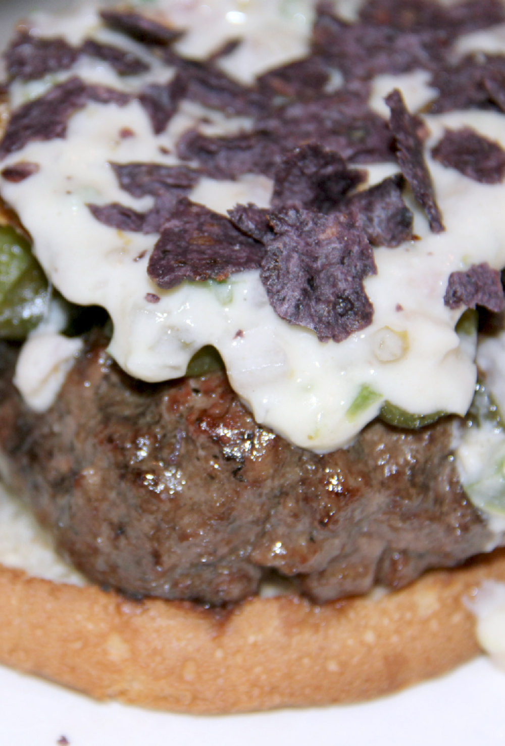 Juicy burger topped with roasted poblano peppers, fried green tomato, melted cheese, and blue corn chips--amazing and delicious!