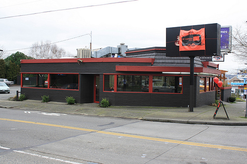 El Camion from Ballard High School looking across 65th; the old rotating RoRo BBQ sign has been draped over with a new El Camion sign.