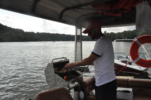 Ari Fingeroth grills up a Nauti dog on his new food boat Nauti Foods. (WTOP/Rachel Nania)