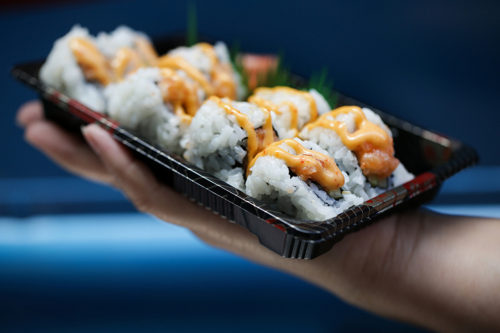 Sushi Daruma food truck owner Ying Alvarez offered a spicy salmon roll at his establishment parked near Seventh Street and Marquette Avenue in downtown Minneapolis. Jennifer Simonson | MPR News