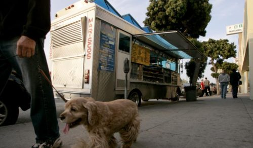 A man walks a dog past a taco truck parked on Venice Blvd. in Los Angeles May 2, 2008. The RAND Corporation partnered with a dozen Los Angeles-area food trucks to test whether healthier menu options would sell. DANNY MOLOSHOK/REUTERS