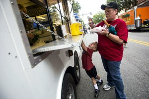 Photographs by Arkansas Democrat-Gazette/MELISSA SUE GERRITS  Gina Bailey gets a corn dog from Garrett's Funnel Cakes &  More at the Main Street Food Truck Festival in downtown Little Rock while Aidan Bailey waits for his order of cotton candy Oct. 5, 2013.