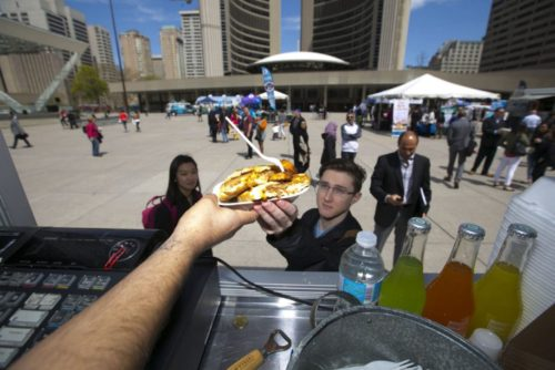 Victor Reinosso, owner of La Novela,  hands lunch to U of T student Brandon Renvina  on Wednesday outside city hall. There are currently  49 permitted mobile food trucks in Toronto.   (CHRIS SO / TORONTO STAR) |