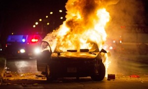 A car burns as a crowd of more than 100 people gathers following the fatal shooting of a man in Milwaukee, Saturday, Aug. 13, 2016 (Calvin Mattheis/Milwaukee Journal-Sentinel via AP).