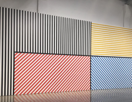 Sol LeWitt, Wall Drawing #368: The wall is divided vertically into five equal parts. The center part is divided horizontally and vertically into four equal parts. Within each part are three-inch (7.5 cm) wide parallel bands of lines in four directions in four colors. In each of the other parts, three-inch (7.5 cm) bands of lines in one of the four directions. The bands are drawn in color and India ink washes. Red, yellow, blue, ink, India ink 3""