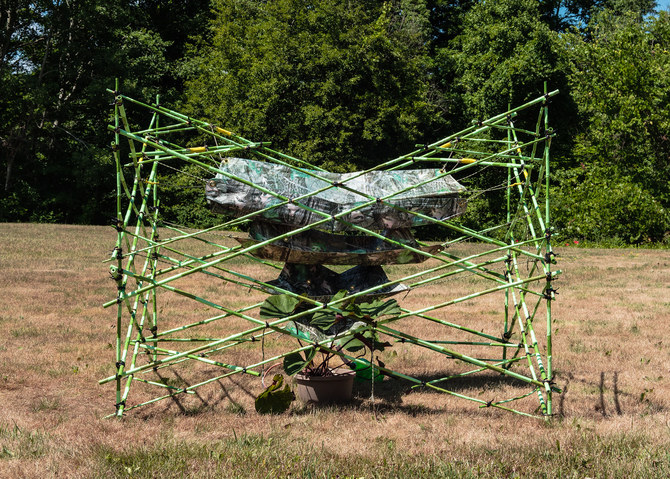 SCULPTURE Stiched camo-printed tarp, thread, brass grommets, bamboo, concrete blocks, rope