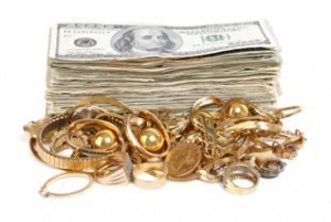 Cash-stack-behind-a-pile-of-scrap-gold-300x201