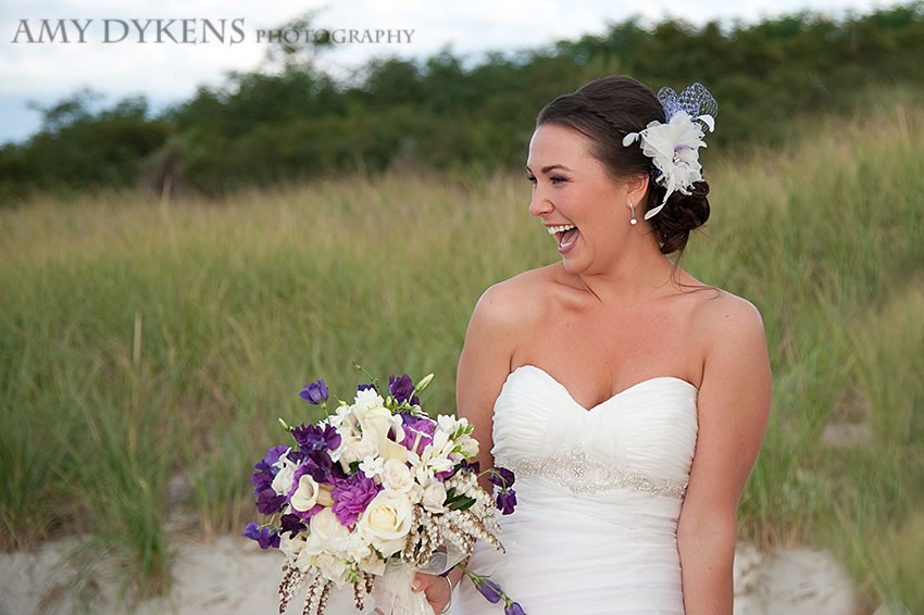 Bride Smiling On The Beach With Purple And White Flowers