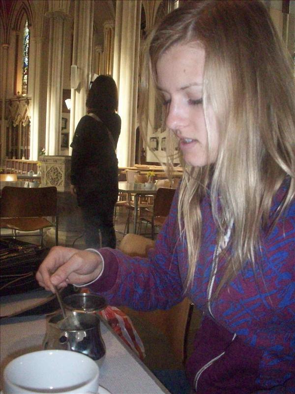 Jess drinking tea in a church