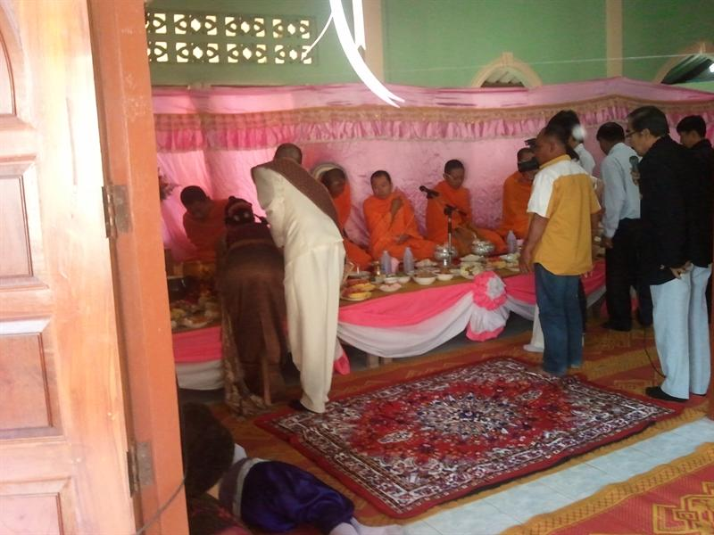 The bride and groom serve the monks food