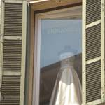 A beautiful wedding dress in a 2nd storoy window.