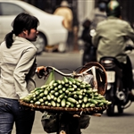 A cucumber vendor pushing her bicycle