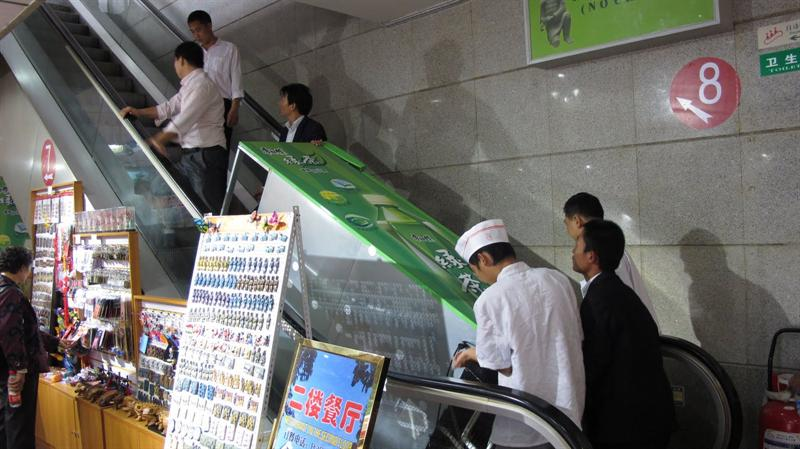 pushing up the big heavy refrigerator on a non-moving escalator--what a man -power they have !