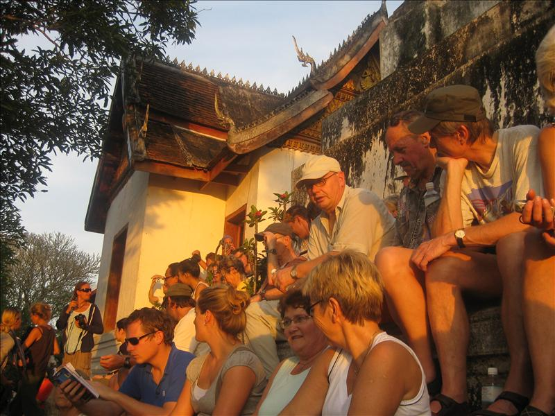Tourists watching the sunset at Wat Chom Si which dominates the city from its perch atop the holy Phu Si Hil