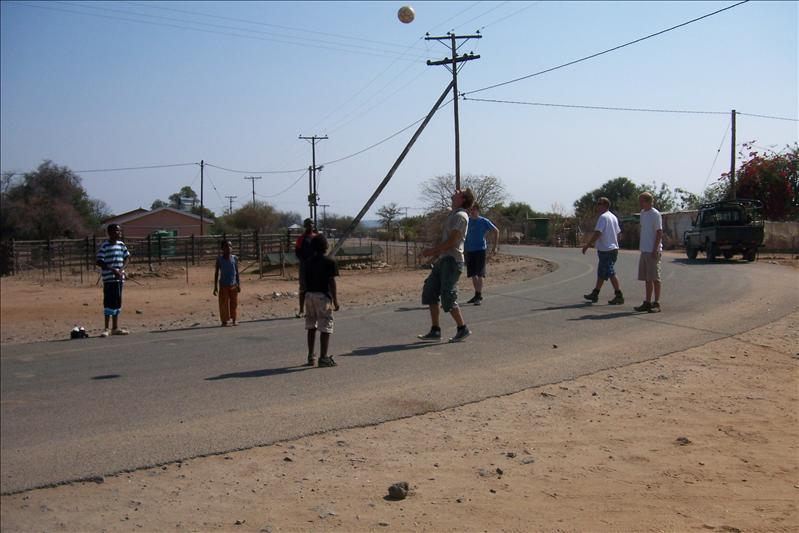 The guys playing soccer with the kids