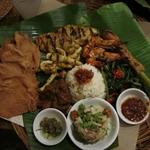 Kuchnia z Indonezji-Bali. Na jednym talerzu, grilowana rybka, kałamarnica, aromatyczna wieprzowina, krewetki, masa mięsna, chyba z jakiś owoców morza upieczona na pałeczce cytrynowej (tak się to tutaj nazywa, tego się nie je, ale daje aromat ziołowo cytrynowy, podawane z niezidentyfikowanym zielonym warzywem, dwoma sosami, jedną sałatką i chrupkami o nazwie Papadam. Wszystko podane jak zwykle na liściu bananowca)