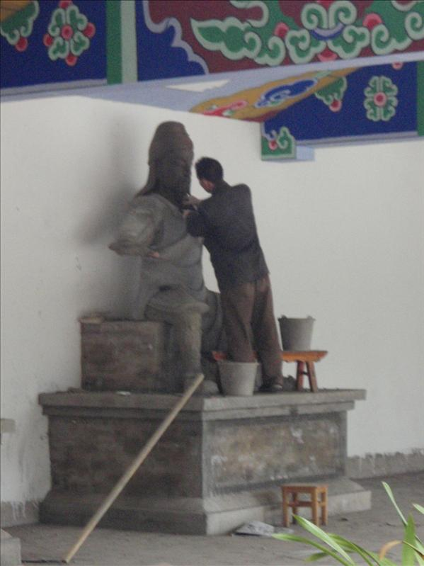man putting face on Buddha