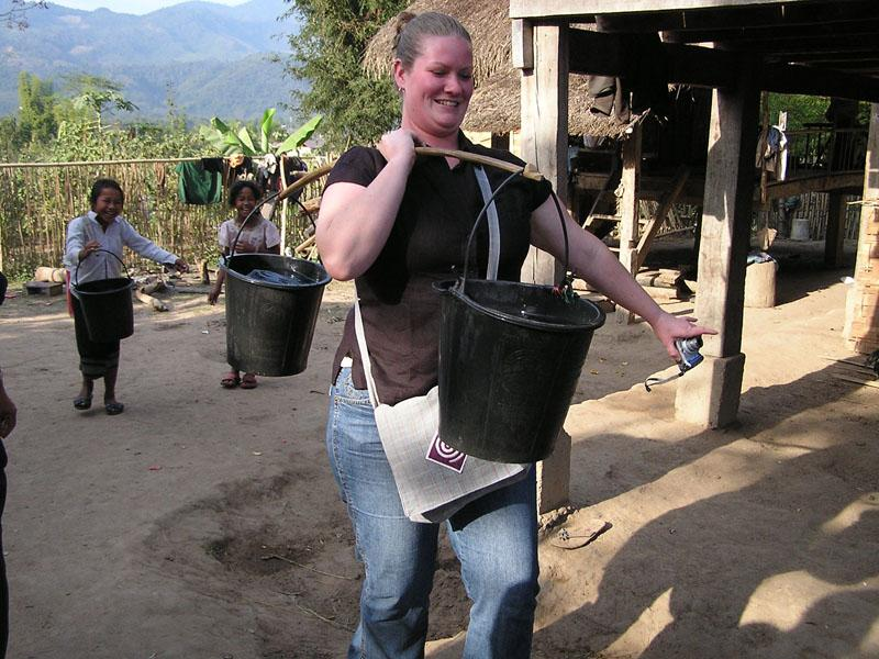 Yeah, see the size of the little girls behind me? They're the ones who haul these water pails up the hill! (I'm still in need of much practice).