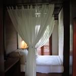 łóżko z moskitierką w domku na palach