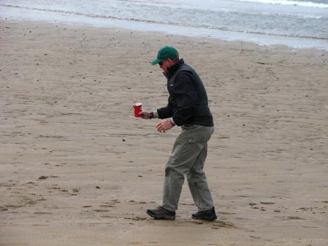 Dad picking up sand for friend