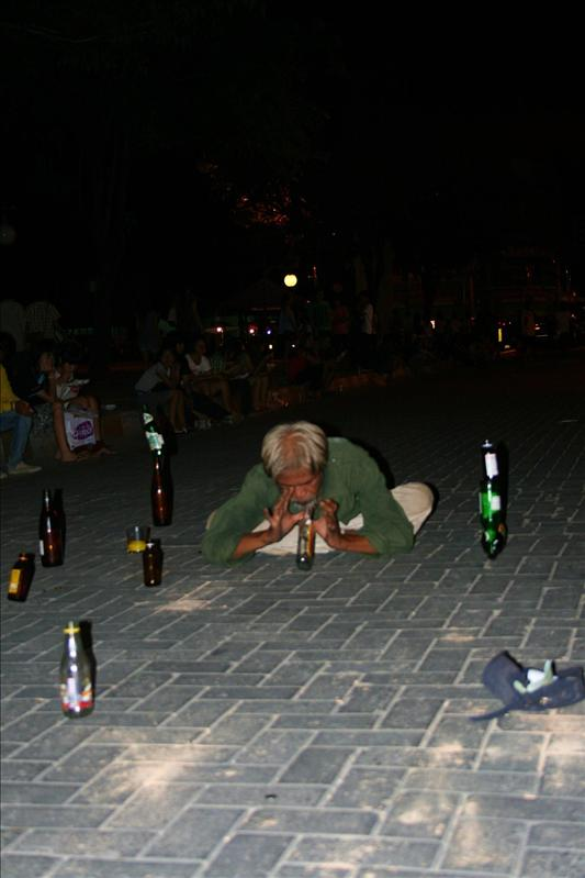 Crazy man, balancing bottles on the pavement.