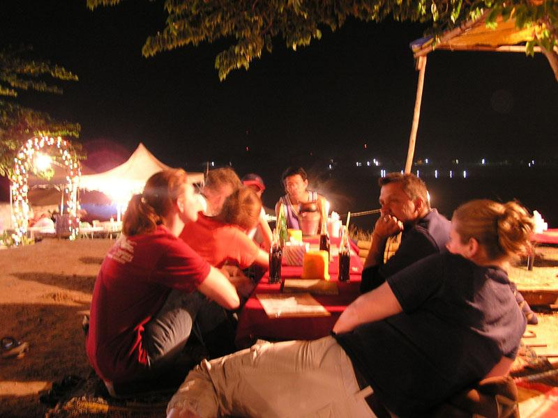 Dinner along the river - traditional eating takes place on floor mats, with the food set on trays.