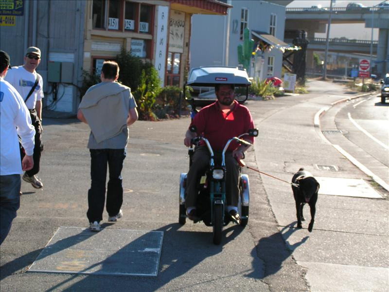 Some guy walking his dog in a scooter