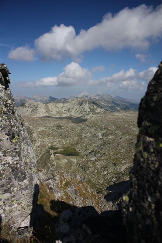 Между скалите се вижда Тевно с част от Белемето. Зад и над Валявишки чукар - Вихрен и Кутело.