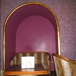 purple tiled wall with a cheetah couch...