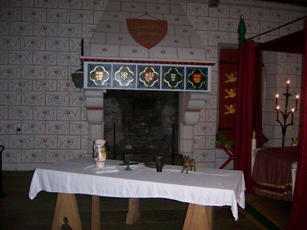 The fireplace and table located at the end of the bedchamber.