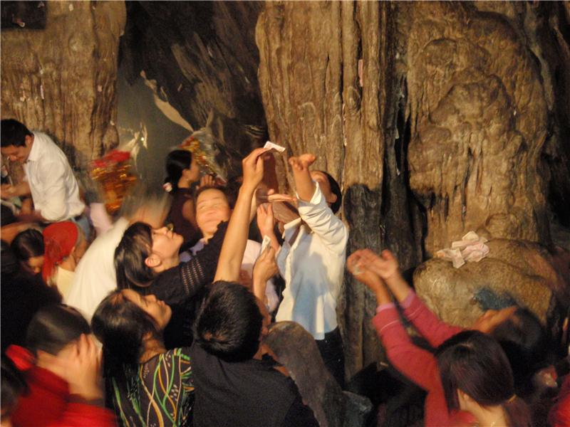Catching drips from the limestone cave ceiling with money