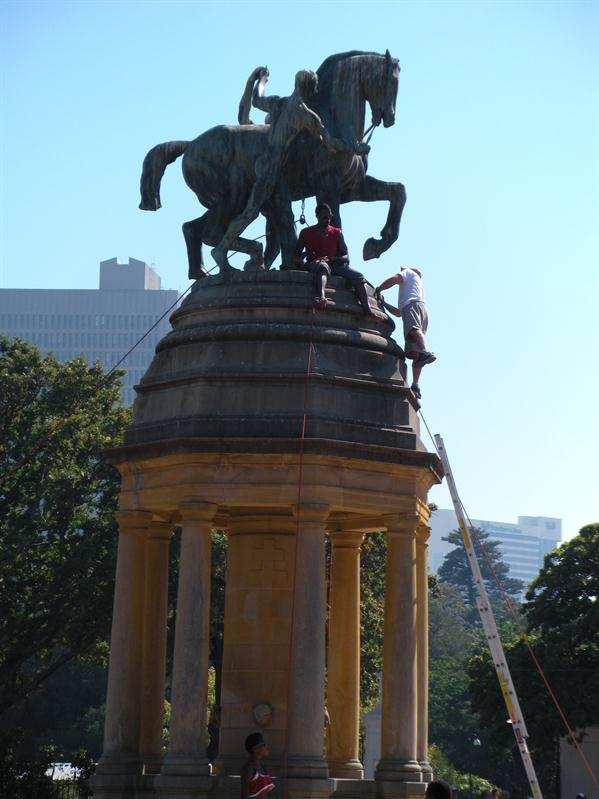 Workers with ropes cleaning statue
