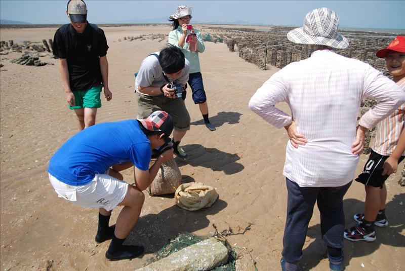 大家爭相拍攝漁人竹簍裡的收獲