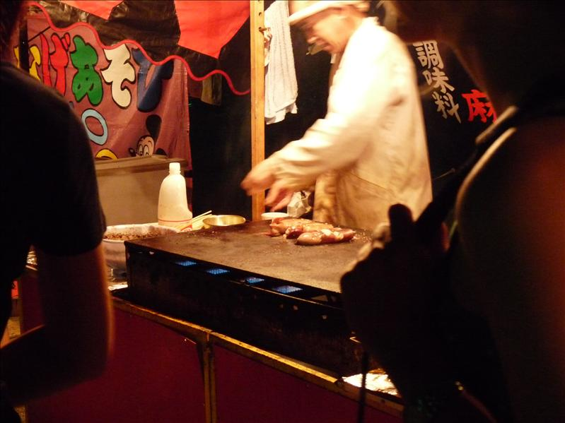 chef is making devil fish ( kind of squid) at one of the many stands surrounding the shrine