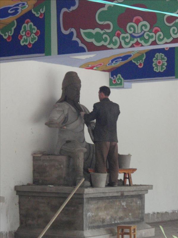 artist fixing Buddha Statue, Lijiang