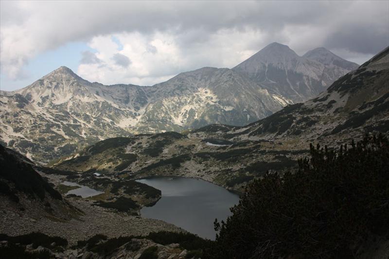 Част от езерата в Бъндеришкия циркус, Муратов връх, Вихрен и Кутело, с тъмни облаци над тях.