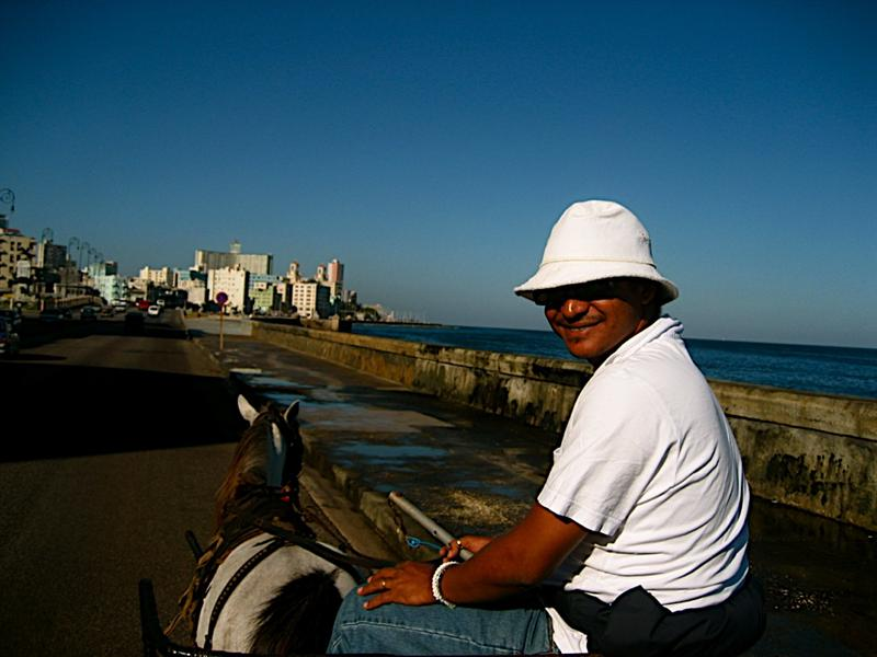 He saw me trying to catch a local taxi and offered me a free ride to the National Hotel, towards the buildings seen in this photo up ahead.Enjoying my early morning horse carriage ride along the Malecon.