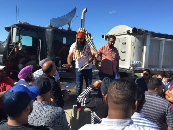 Jagroop Singh Bangli, a two-truck owner-operator, calls on the crowd to expand the protest.