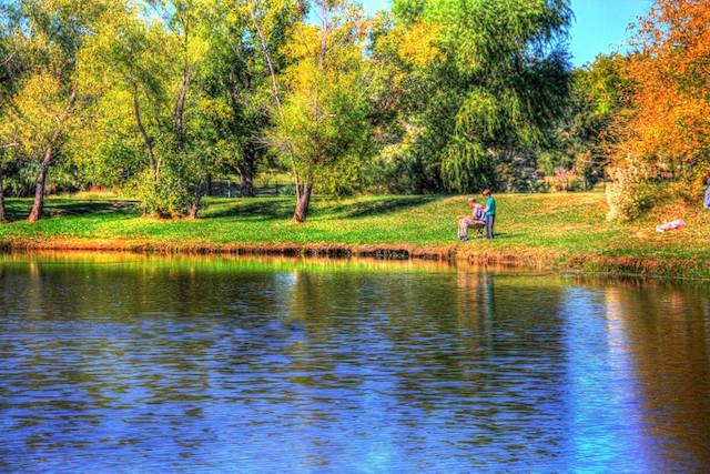 Couple sits by a lake.