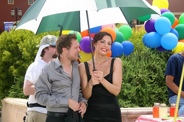 A couple under an umbrella outside.