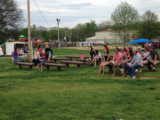 crowd of people gathered on benches at a community event