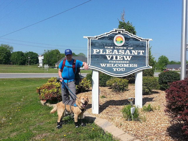 man and guide dog standing next to a pleasant view town sign
