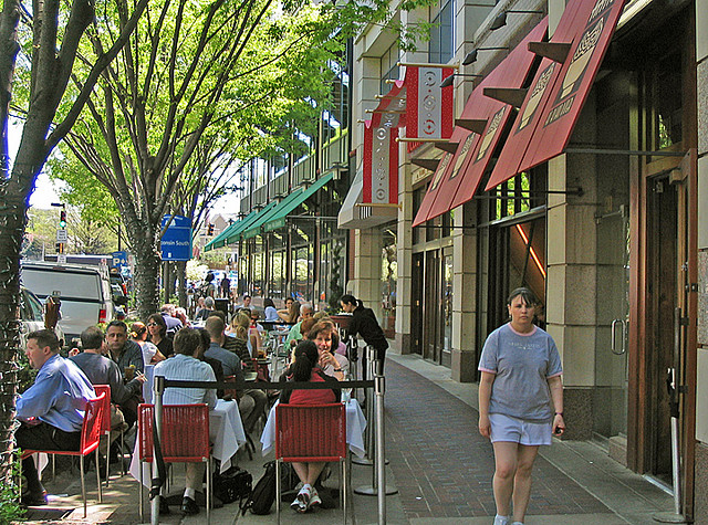 People eat at a sidewalk cafe.