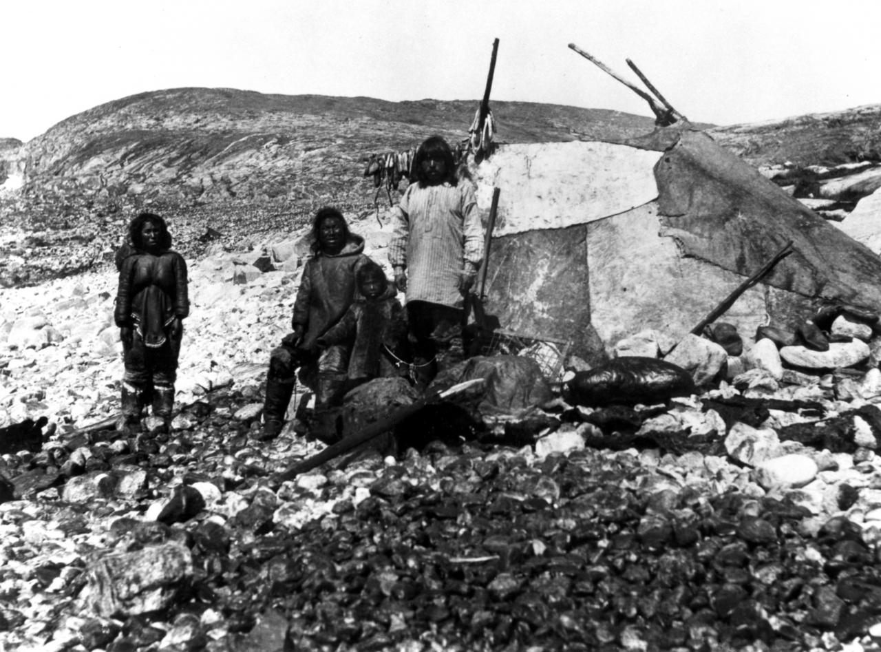 Black and white picture of 3 adults and an Inuit child in front of a skin tent. We can see a harpoon in front of them.